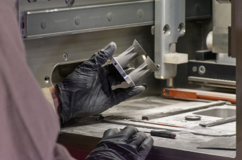 Additive manufacturing with 7A77.60L aluminum alloy: An HRL scientist completes visual inspection of 3D-printed micro-thrusters after build completion .